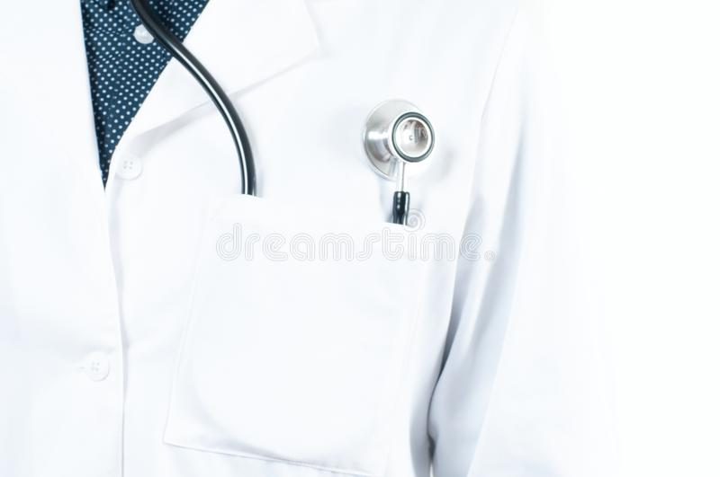 Stethoscope in a pocket of a doctor`s white lab coat. Close up of a stethoscope in a pocket of a doctor`s white lab coat royalty free stock photo