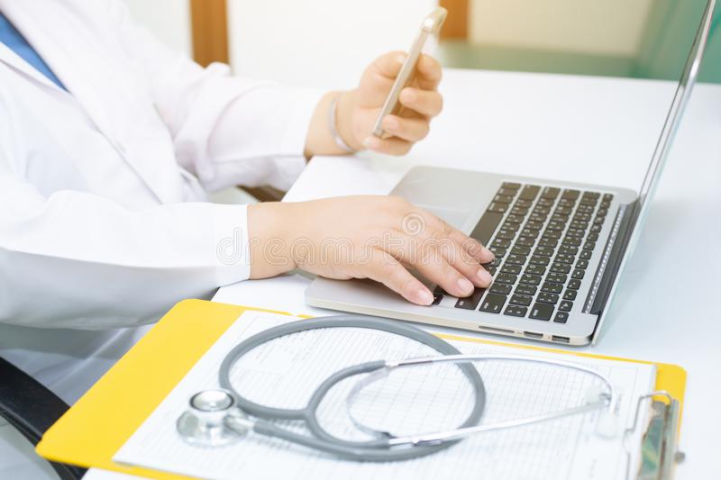 Stethoscope and Doctor working an Laptop on desk in hospital. Stethoscope on prescription clipboard andDoctor working an Laptop on desk in hospital royalty free stock photography