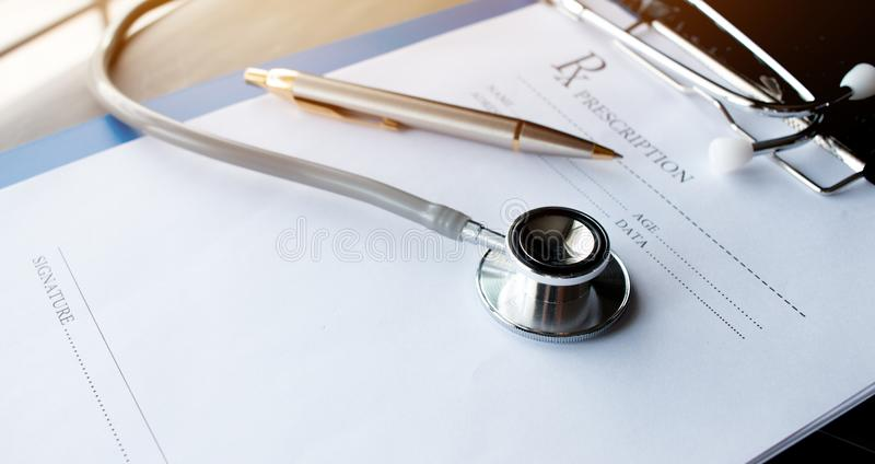 Stethoscope and record information paper folder with pen on Laptop, smart phone at medicine doctor work, on blur patient in royalty free stock photos