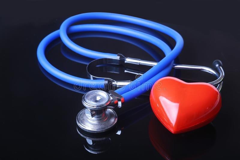 Stethoscope, Red heart and blood pressure meter on black mirror background. Selective focus. stock photo