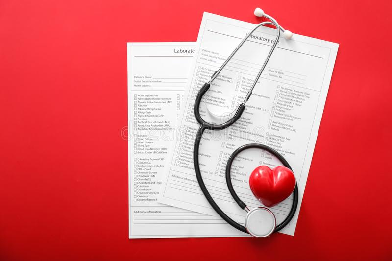 Stethoscope with red heart and lists of laboratory tests on color background. Health concept stock image