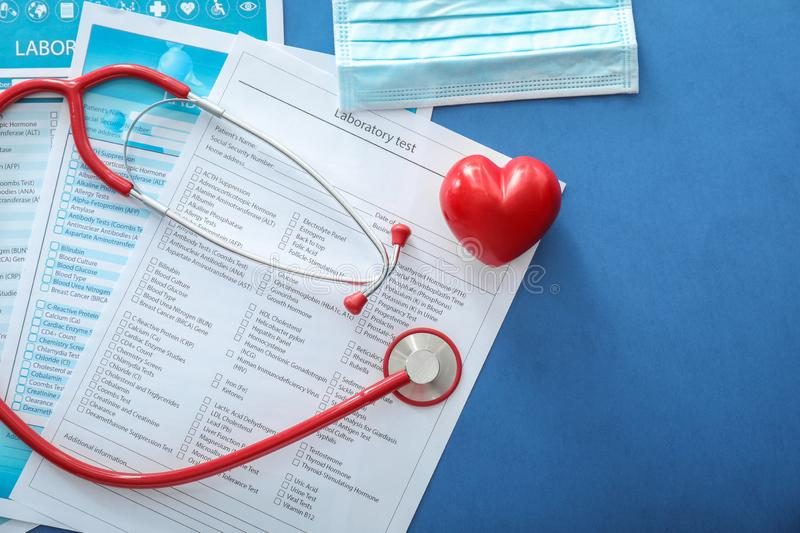 Stethoscope with red heart and lists of laboratory tests on color background. Health concept royalty free stock images
