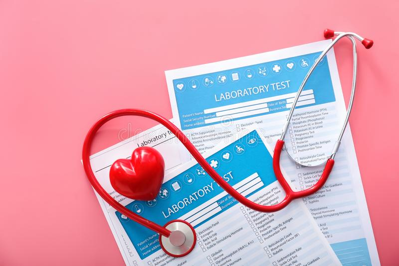 Stethoscope with red heart and lists of laboratory tests on color background. Health concept stock photography