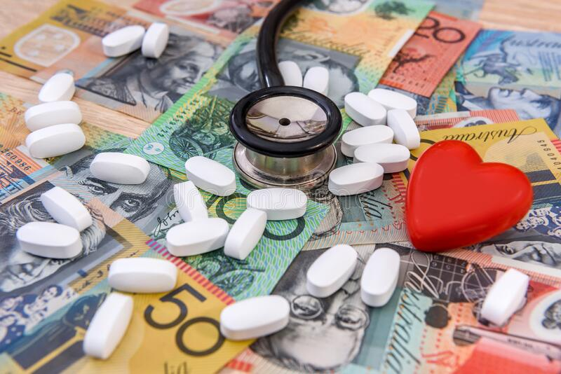 Stethoscope with red heart and pills on australian dollars.  royalty free stock photography