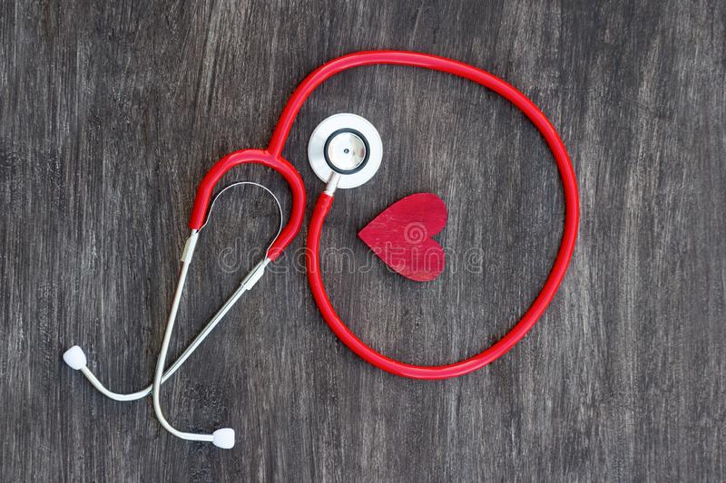Stethoscope and red heart on wooden background. Health care concept stock image