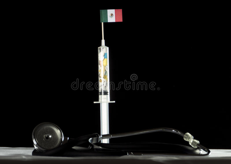 Stethoscope and syringe filled with drugs injecting the Mexican flag on a black background stock photos