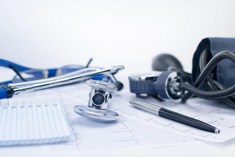 Stethoscope on the working table of a cardiologist. Tonometer, electrocardiogram and notepad with phonendoscope, medical stock image