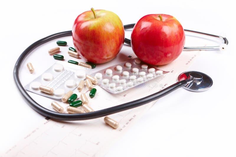 Stethoskop, Äpfel, Pillen und EKG Diagramm lizenzfreies stockbild