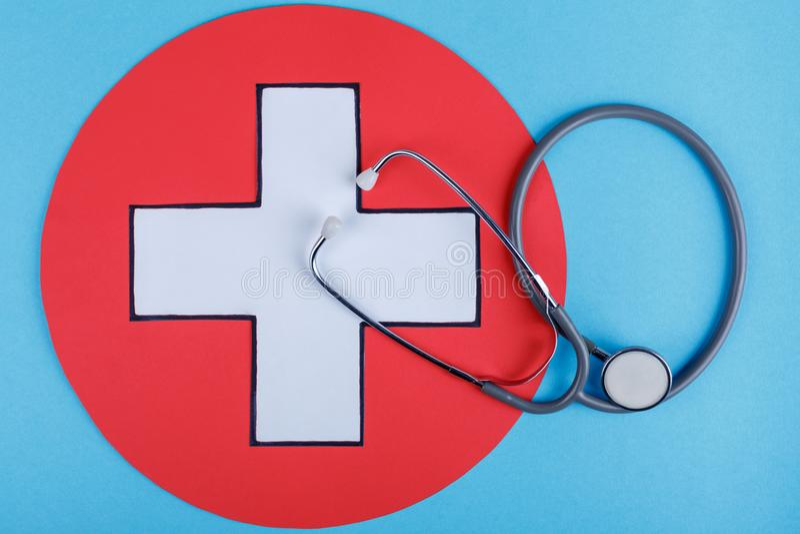 Stethoskop auf einem blauen Hintergrund mit dem Bild eines medizinischen Zeichens Das Konzept von Medizin Beschneidungspfad einge stockfotografie