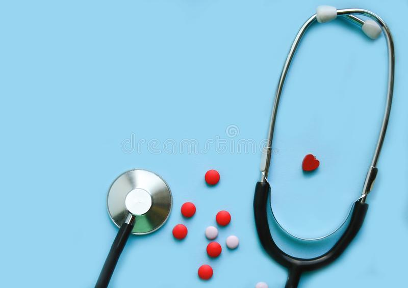 Stethoskop auf einem blauen Hintergrund mit Pillen und einem roten Herzen, freier Raum lizenzfreies stockfoto