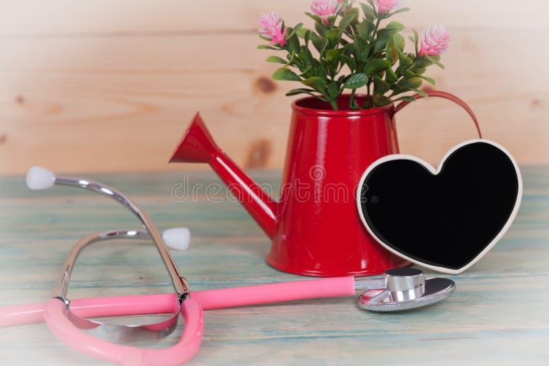 Stethoskop auf Holz mit schwarzem Herzen stockfotografie
