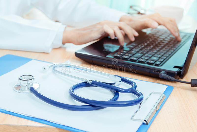 Stethoskop auf Schreibtisch mit Doktor unter Verwendung der DigitaltechnikLaptop-Computers lizenzfreies stockbild