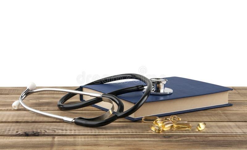Stethoskop, blaues Buch und Fischölkapseln auf einem Holztisch stockfotografie