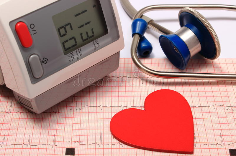 Stethoskop, Herzform, Blutdruckmonitor auf Elektrokardiogramm stockfotografie