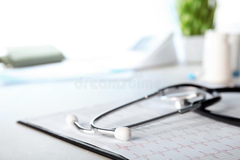 Stethoskop, Kardiogramm und Formen auf Tabelle, Nahaufnahme stockbild