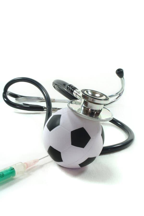 Stethoskop mit Fußball und Spritze stockbilder