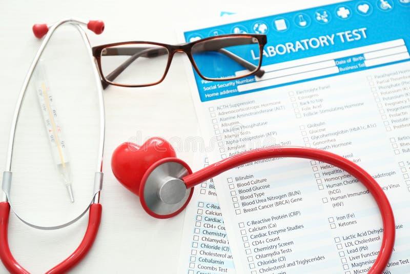 Stethoskop mit rotem Herzen und Listen von Laborversuchen auf weißem Hintergrund Stellen Sie sch?tzende Schablone und die Pille g stockbild