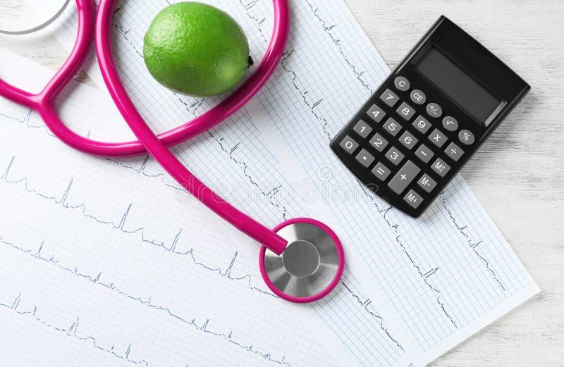 Stethoskop mit Taschenrechner und Kardiogramme auf hölzernem Hintergrund Stellen Sie sch?tzende Schablone und die Pille gegen?ber lizenzfreies stockfoto