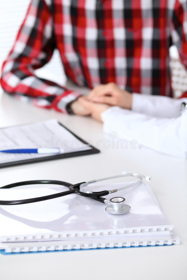 Stethoskop nahe bei der Hand von Doktor ihrem männlichen Patienten versichernd Medizinische Ethik und Vertrauenskonzept lizenzfreie stockbilder