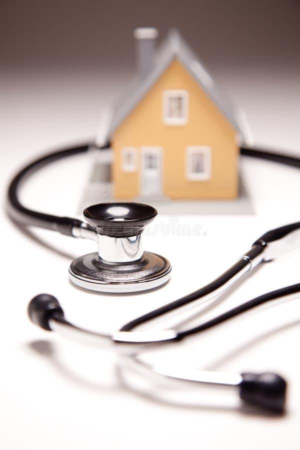 Stethoskop-und Baumuster-Haus auf Gradated Hintergrund lizenzfreies stockbild