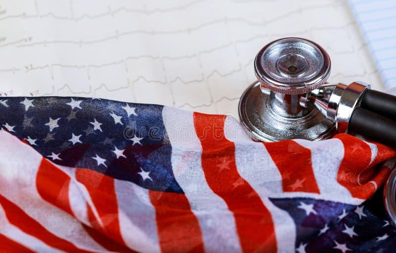 Stethoskop und ECG-Kardiogramm auf einem Papier auf amerikanischer Staatsflagge stockfotos