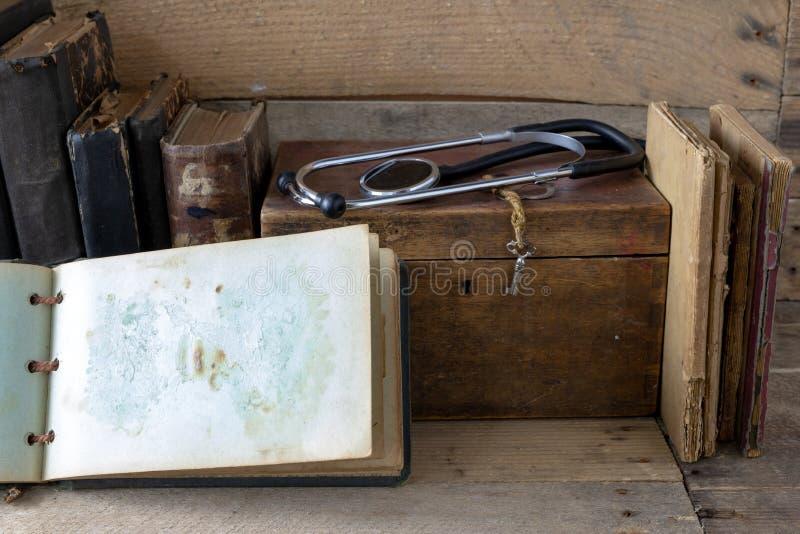Stethoskop und ein Fall auf einem alten Schreibtisch Medizinische Zeitschriften und MED stockbilder