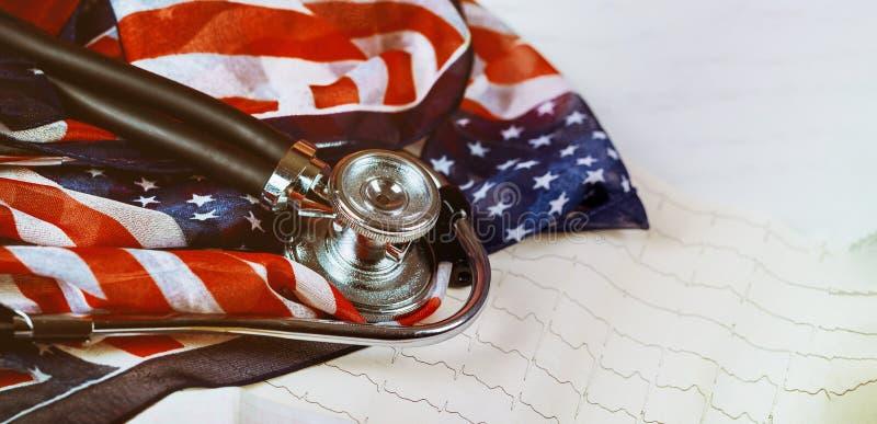 Stethoskop und Kardiogramm auf Tabelle US-Flagge stockfotografie