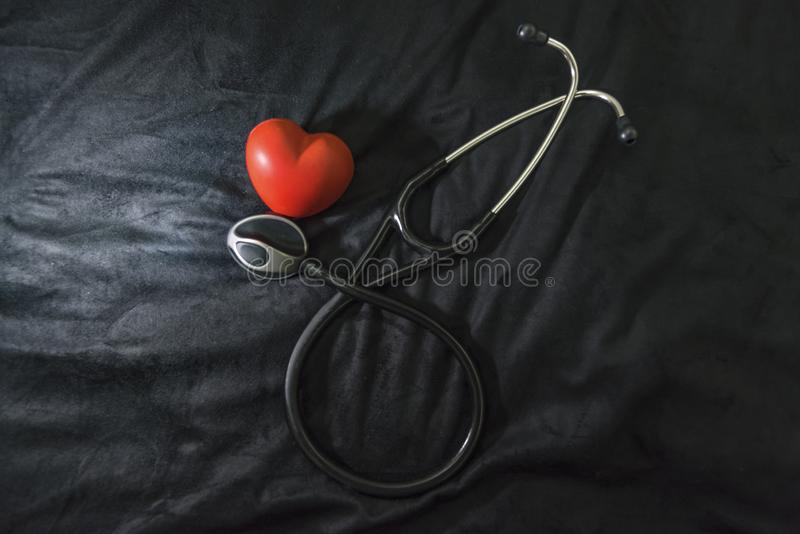 Stethoskop und rote Herzzahl auf dem schwarzen Hintergrund, Innen stockbilder