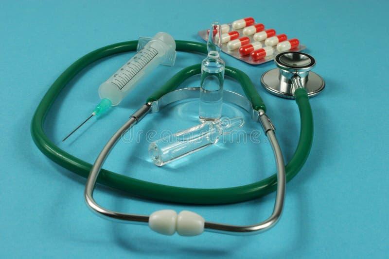 Stethoskop und Spritze auf blauem Hintergrund lizenzfreie stockbilder
