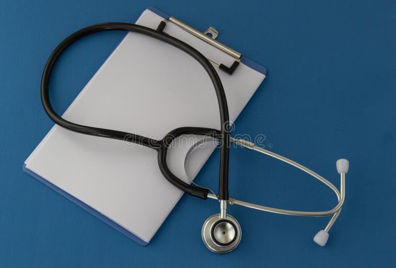 Stethoskop, Verordnung, auf blauem Hintergrund Das Konzept von Medizin lizenzfreies stockbild