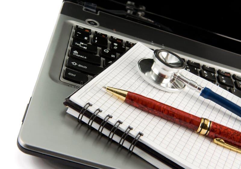 Stetoscopio al computer portatile del taccuino isolato su bianco fotografia stock