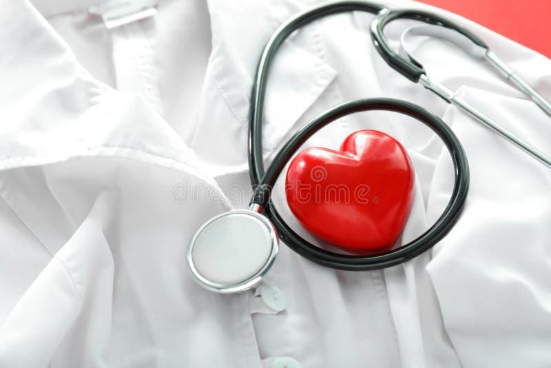 Stetoscopio con il cappotto rosso di medico e del cuore, primo piano Concetto di salute immagini stock