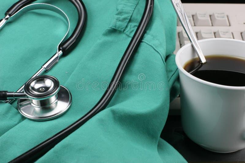Stetoscopio con il grembiule, il caffè & la tastiera. fotografia stock libera da diritti