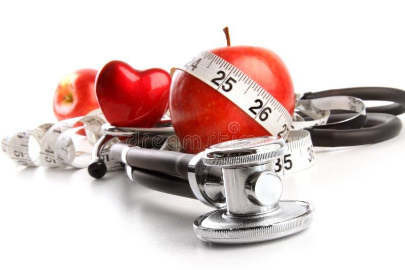 Stetoscopio con le mele rosse su un bianco fotografia stock