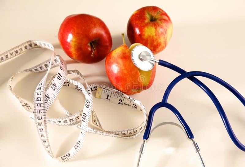 Stetoscopio con le mele rosse su un fondo bianco fotografia stock libera da diritti