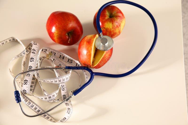 Stetoscopio con le mele rosse su un fondo bianco fotografie stock libere da diritti