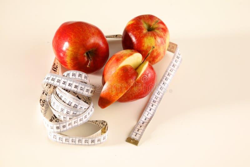 Stetoscopio con le mele rosse su un fondo bianco immagine stock libera da diritti