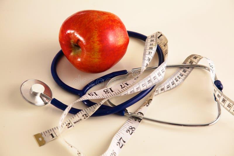 Stetoscopio con le mele rosse su un fondo bianco fotografie stock