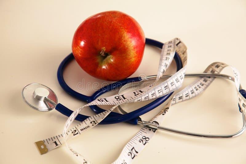 Stetoscopio con le mele rosse su un fondo bianco fotografia stock
