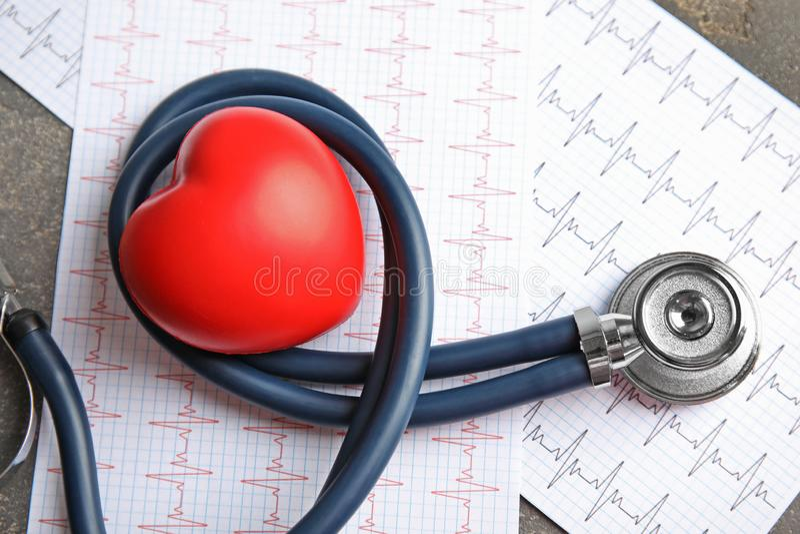 Stetoscopio, cuore rosso e cardiogrammi sulla tavola cardiologia immagini stock