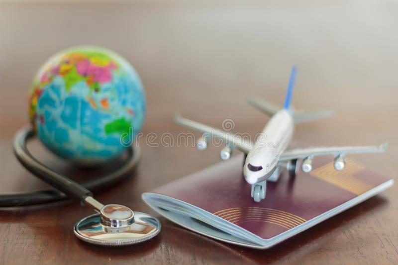 Stetoscopio, documento del passaporto, aeroplano e globo Concetto di assicurazione di viaggio e di sanità immagini stock libere da diritti