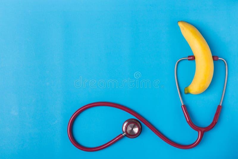 Stetoscopio e banana gialla su fondo blu Per il pene degli uomini fotografia stock