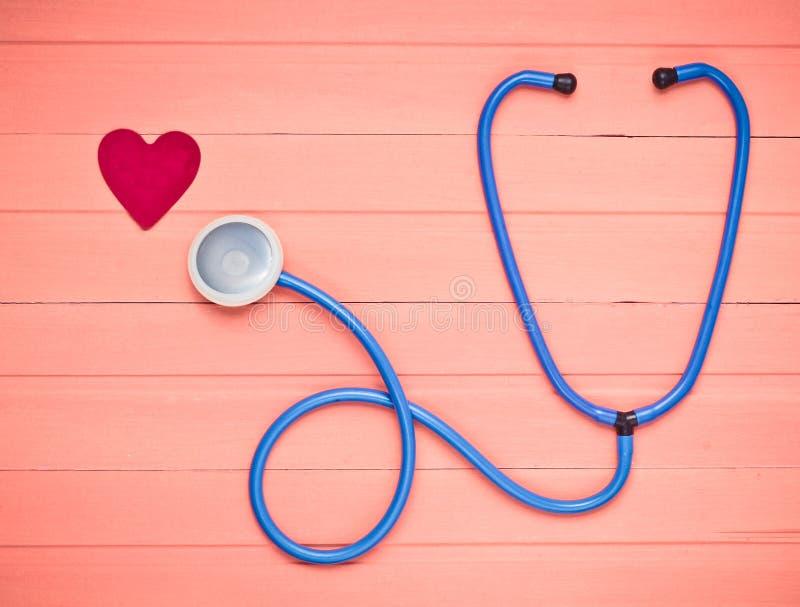 Stetoscopio e cuore sulla tavola di legno di rosa pastello Attrezzatura di cardiologia per la diagnostica delle malattie cardiova fotografia stock