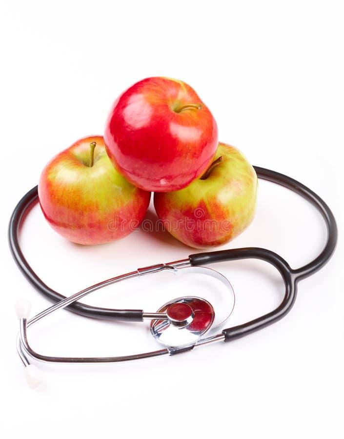 Stetoscopio e mele sopra priorità bassa bianca immagini stock