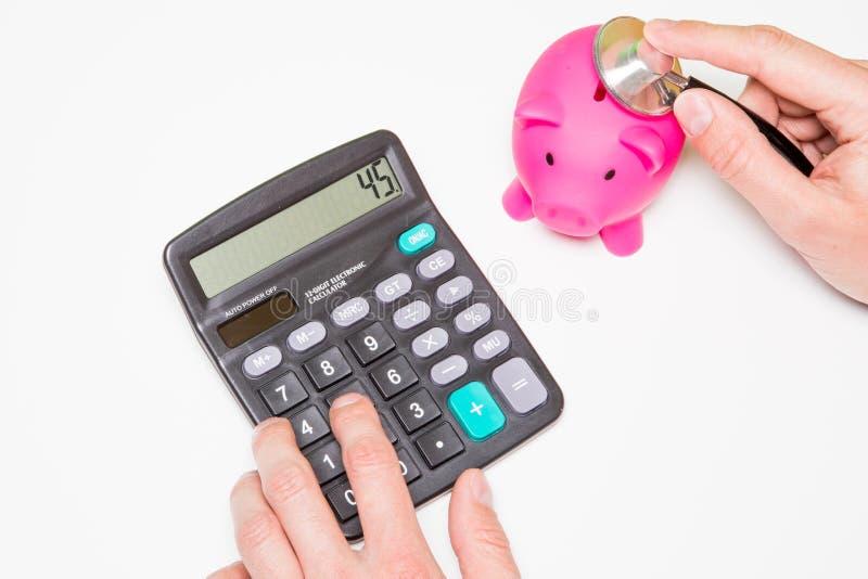 Stetoscopio e porcellino salvadanaio per il concetto finanziario del controllo sanitario fotografia stock