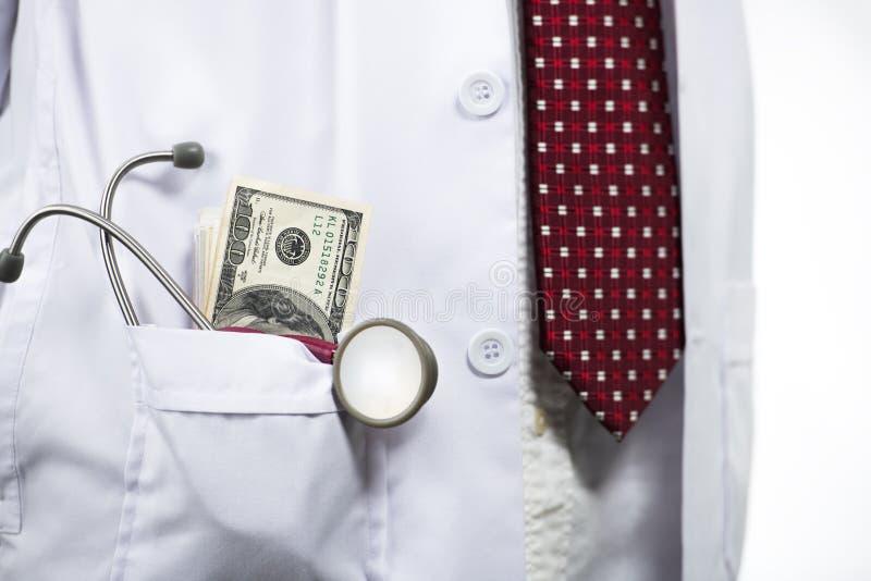 Stetoscopio e soldi in tasca dell'abito di medico immagini stock