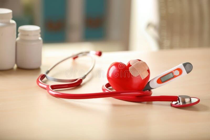 Stetoscopio medico e cuore rosso con gesso sulla tavola leggera Concetto di cardiologia immagini stock