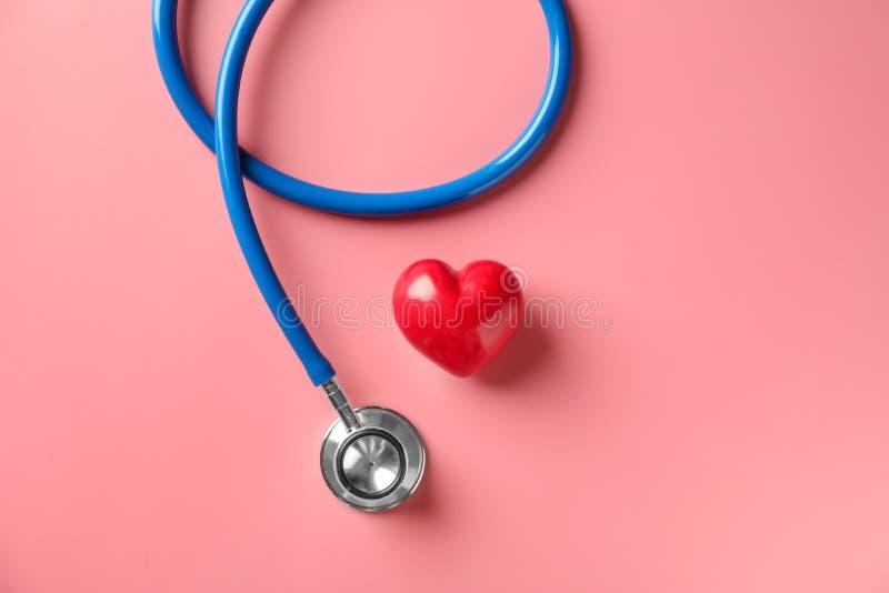 Stetoscopio medico e cuore rosso sul fondo di colore Concetto di cardiologia fotografie stock libere da diritti