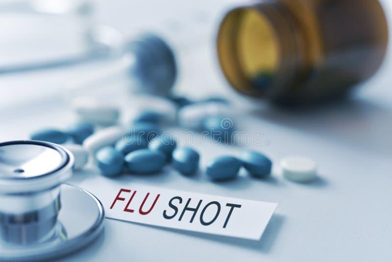 Stetoscopio, pillole e iniezione antinfluenzale del testo fotografie stock libere da diritti