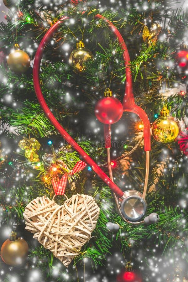 Stetoscopio rosso che appende su un albero di Natale decorato Natale medico immagini stock libere da diritti